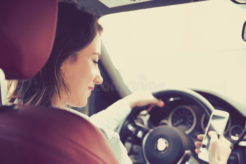 送文本的美丽的年轻女实业家,当驾驶到工作时 库存图片