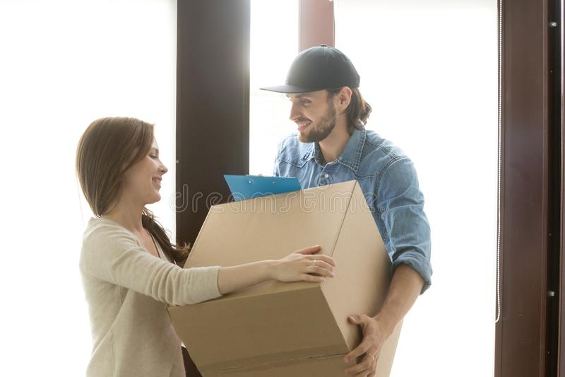 送货业务概念,接受箱子的妇女从传讯者在ho 免版税库存图片