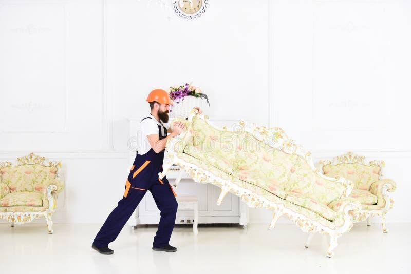 送货业务概念 装载者移动沙发,长沙发 有胡子、工作者总体的和盔甲的人提起沙发,白色 图库摄影