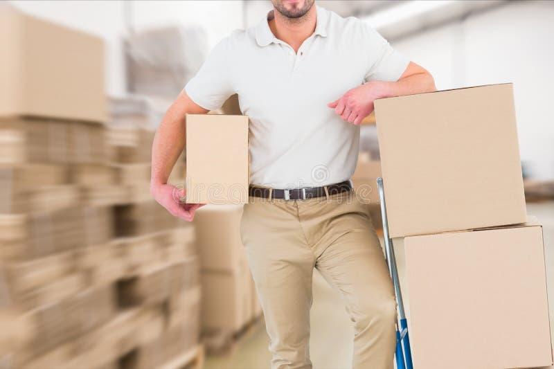 送货人在拿着包裹的仓库里 免版税库存图片