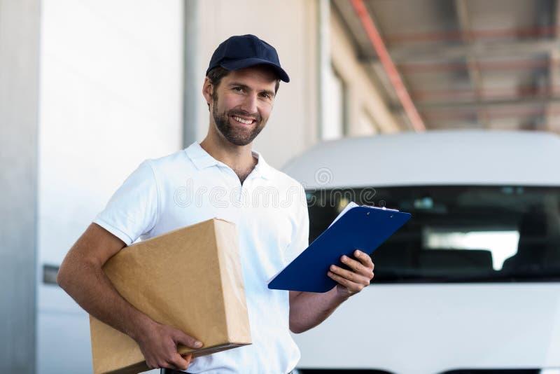 送货人拿着一个纸板箱和剪贴板和摆在 免版税库存图片