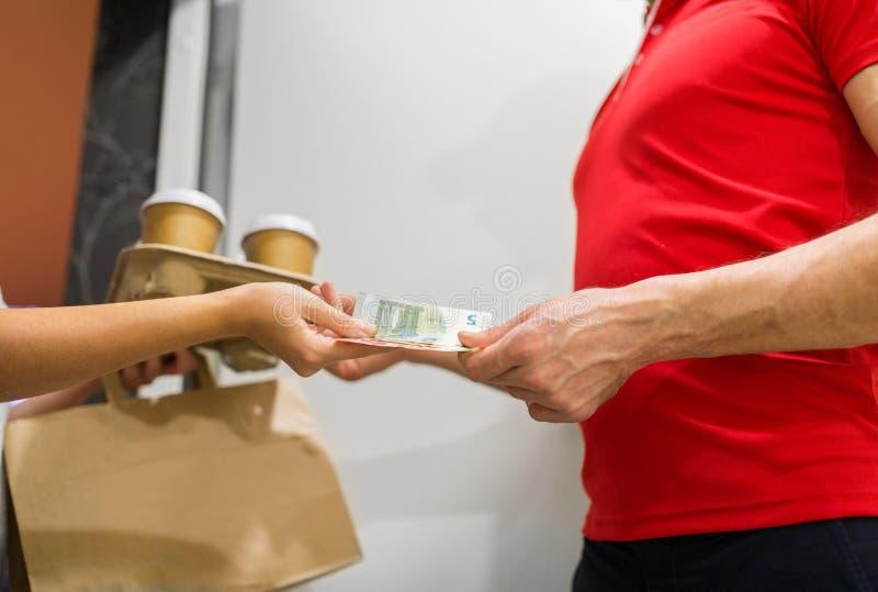 送货人用咖啡和食物在顾客家 免版税库存照片