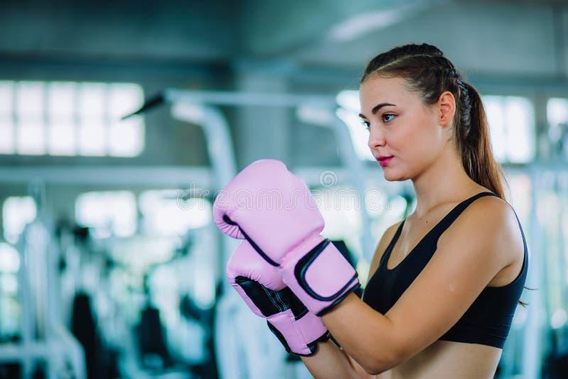 适合击中在健身房的美女拳击手巨大的吊袋锻炼类 做直接命中动态运动的拳击手妇女 免版税库存照片