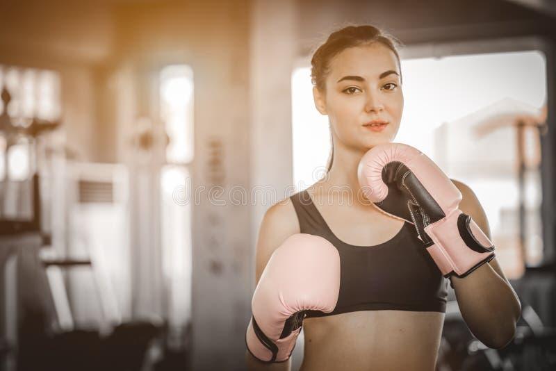 适合击中在健身房的美女拳击手巨大的吊袋锻炼类 做直接命中动态运动的拳击手妇女 免版税库存图片