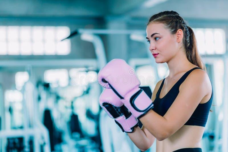 适合击中在健身房的美女拳击手巨大的吊袋锻炼类 做直接命中动态运动的拳击手妇女 库存图片