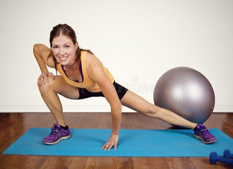 适合女性舒展在健身房 免版税库存图片