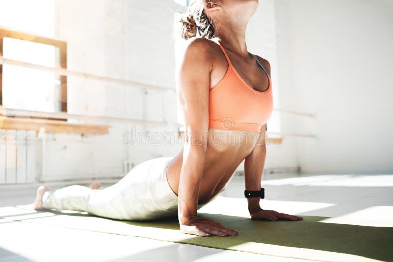 适合少妇实践的瑜伽室内白色类画象  在晴朗的健身房的英俊的女孩实践眼镜蛇asana 免版税库存图片