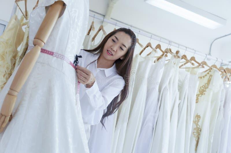 适合新娘婚装的专业婚礼礼服设计师对妇女 免版税图库摄影