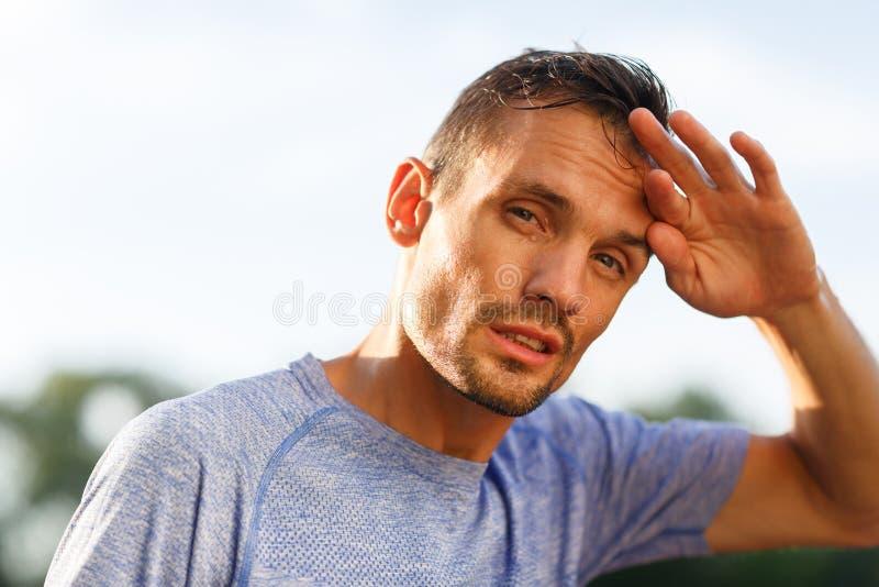 适合的人弯曲了头并且抹前额与他的手指 库存图片