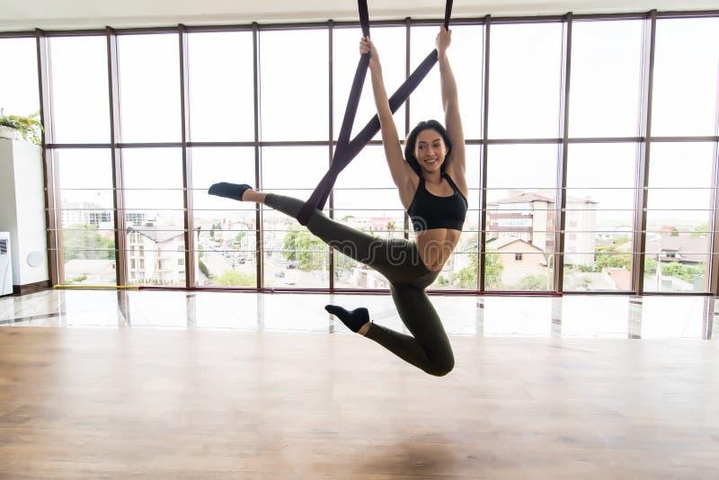 适合的俏丽的做年轻女人佩带的sportwear飞行在健身训练的瑜伽伸展运动在有大窗口的瑜伽演播室 免版税库存图片