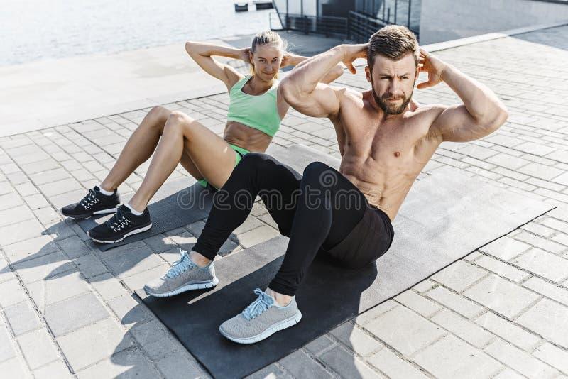 适合的做健身的健身妇女和人在城市行使户外 库存照片