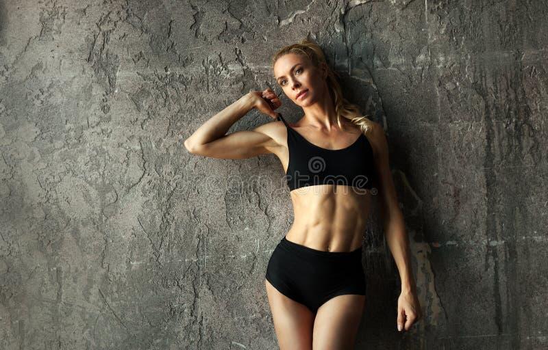 适合的女性健身式样摆在和显示她的与强和被晒黑的腹肌的强健的身体在混凝土墙前面 免版税库存图片