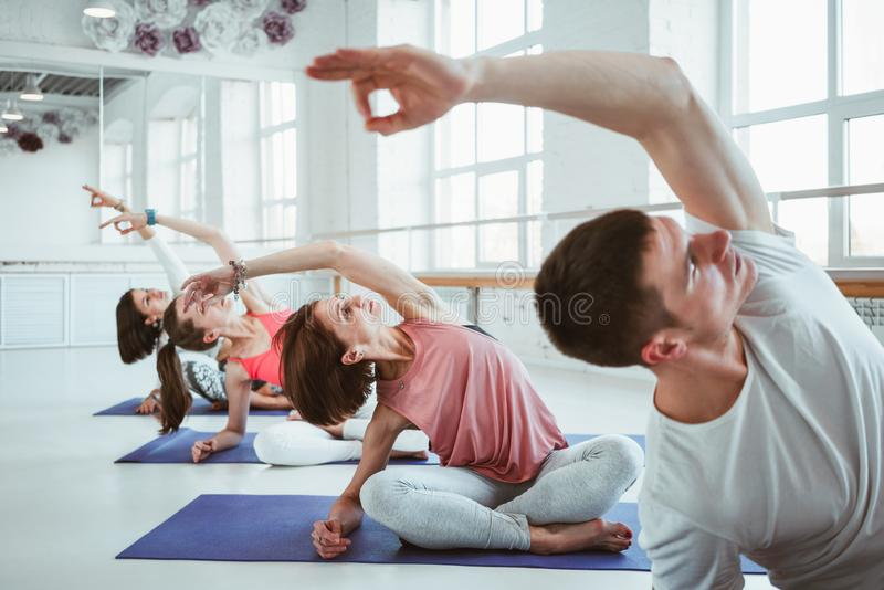 适合的妇女和人实践的瑜伽姿势在健身类 做在白色健身房的小组健康坚强的人民适合的锻炼 免版税库存图片