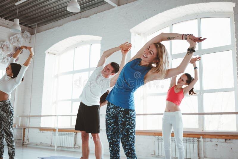 适合的妇女和人实践的瑜伽姿势在健身类 免版税库存照片