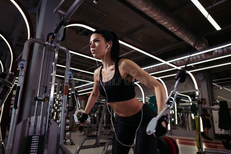 适合的妇女执行与锻炼机器缆绳天桥的锻炼在健身房 免版税库存图片