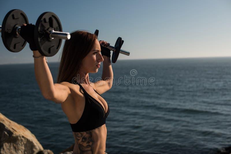 适合的室外妇女举的重量- 免版税库存照片
