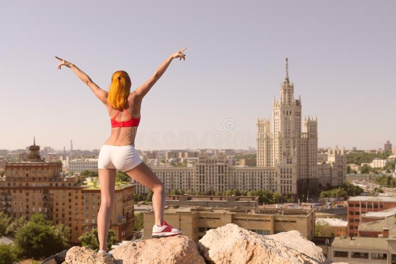 适合的少妇用在城市上的被举的手 免版税库存照片