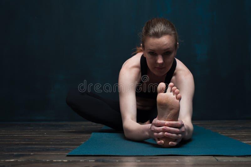 适合的白种人女孩实践的瑜伽户内 免版税库存图片