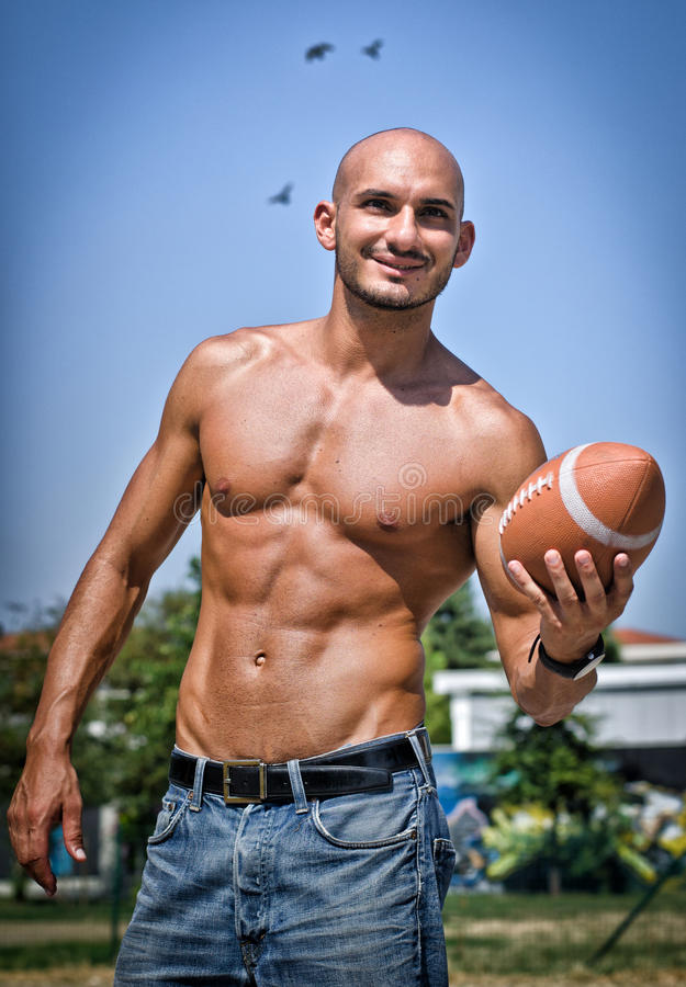 适合的年轻人赤裸与橄榄球 库存图片