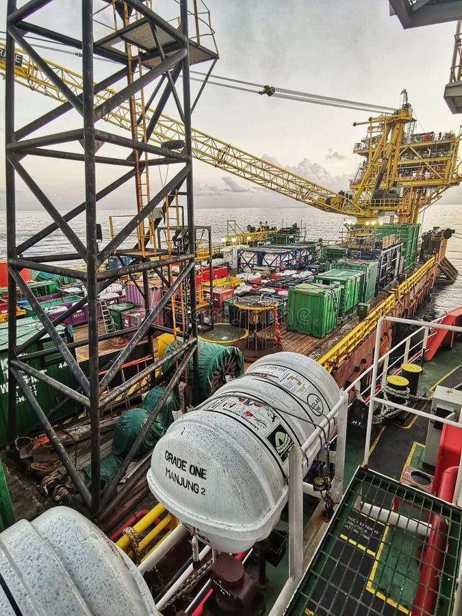 适应工作驳船被栓对石油平台在美好的日落期间 免版税库存图片