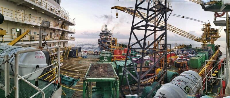 适应工作驳船被栓对石油平台在美好的日落期间 库存图片
