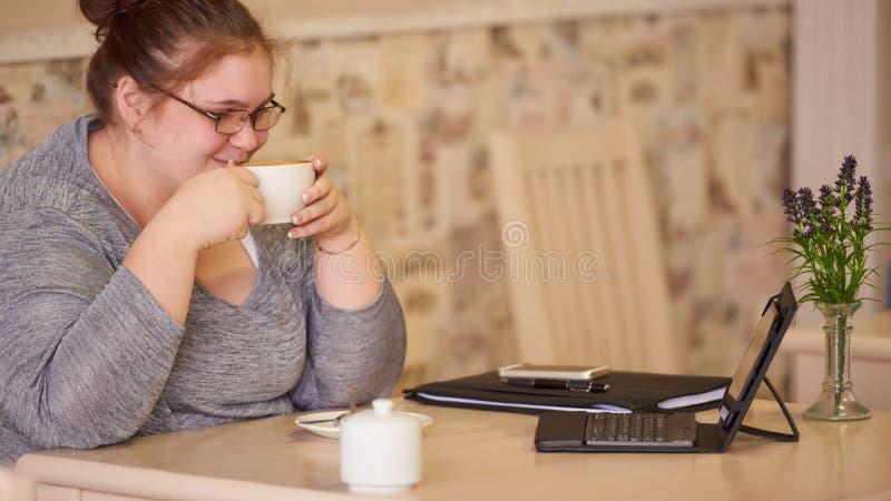 肥胖老女聊天视频_适度地坐在咖啡馆的肥胖女实业家,当拿着咖啡时