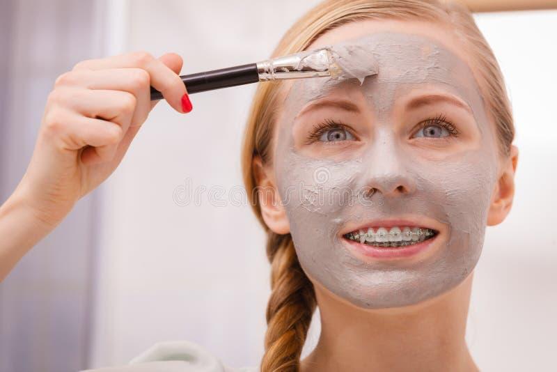 适用与刷子黏土泥面具的妇女于她的面孔 库存图片