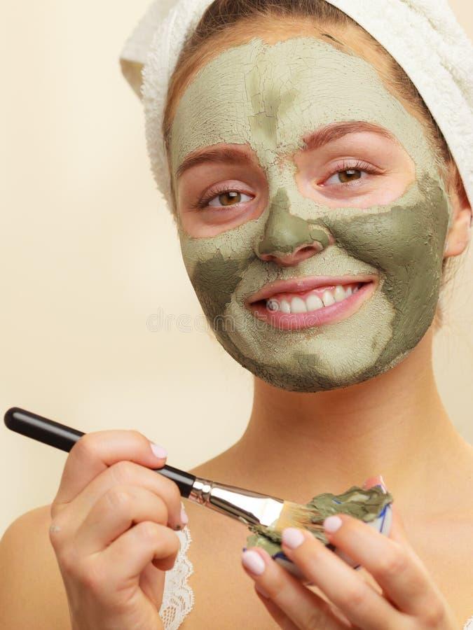 适用与刷子黏土泥面具的妇女于她的面孔 免版税库存照片