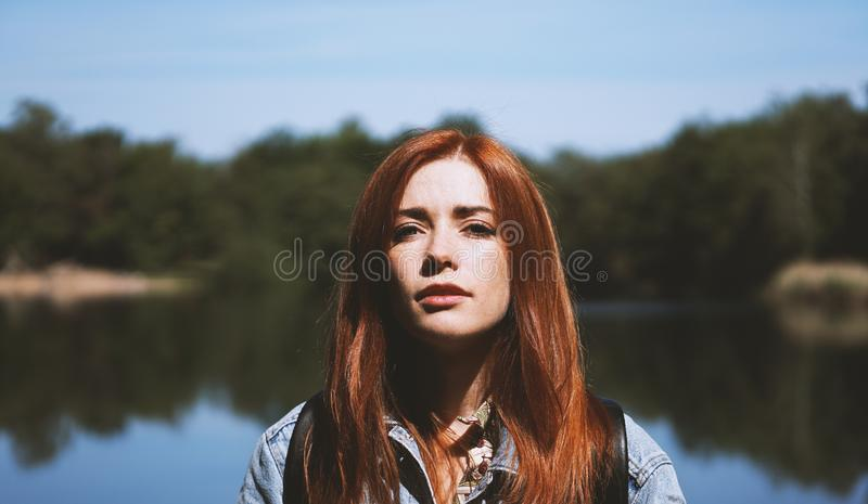 适用于户外的苛刻的光的年轻女人支持的湖 免版税库存照片