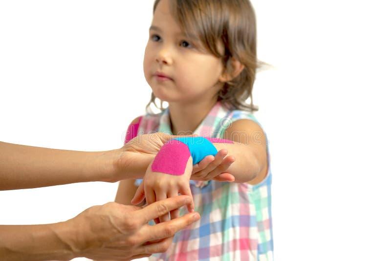 适用于kinisiology磁带的母亲她的女儿伤害手 图库摄影