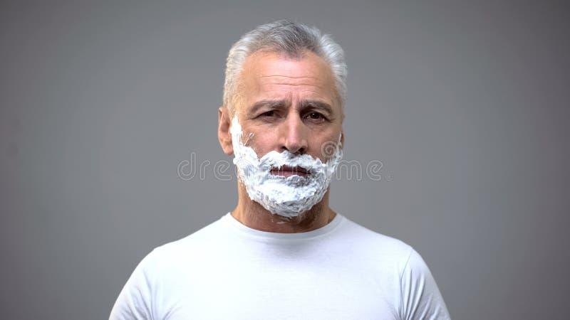 适用刮泡沫于他的面孔的成熟人,变老的skincare奶油,润湿 免版税库存照片