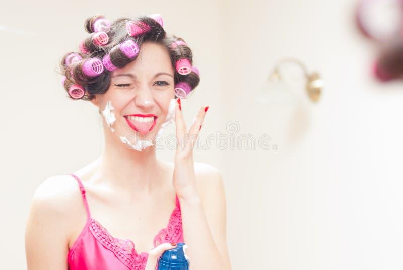 适用刮泡沫于她的面孔的美丽的滑稽的女孩 免版税库存照片