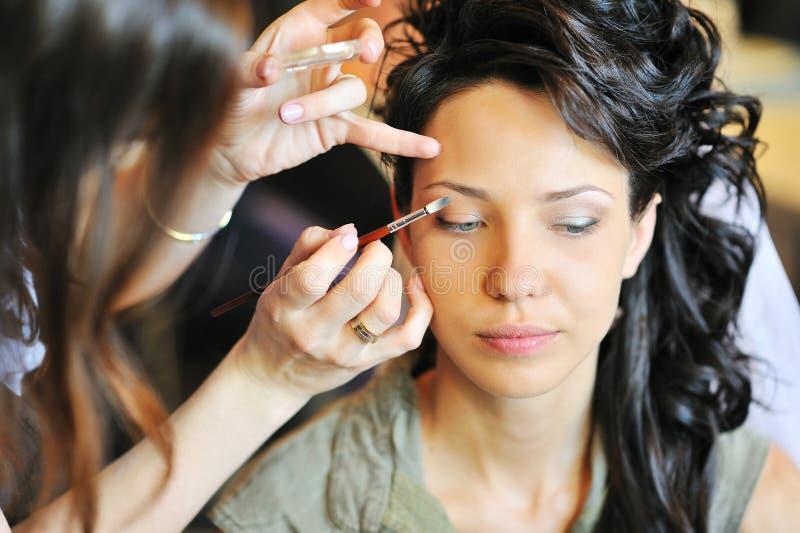 适用婚礼构成的新娘由化妆师 免版税库存图片