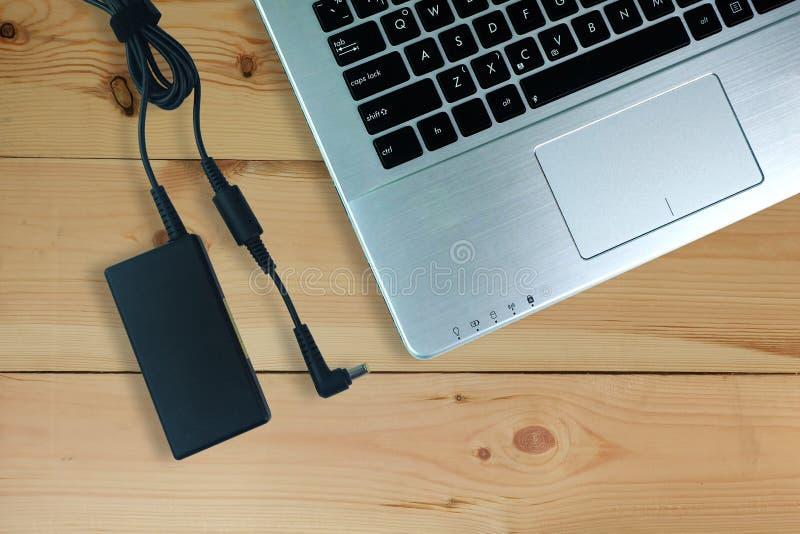 适配器便携式计算机电源线充电器在木地板,顶视图上的 免版税库存照片