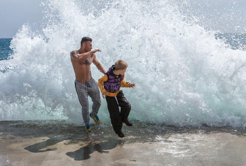 逃离海浪的父子 库存照片