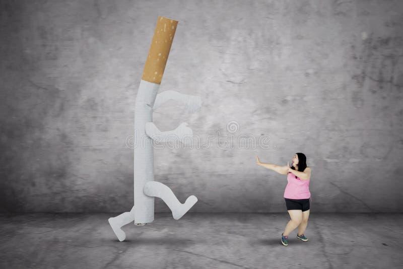 逃脱从香烟的肥胖妇女 免版税库存照片
