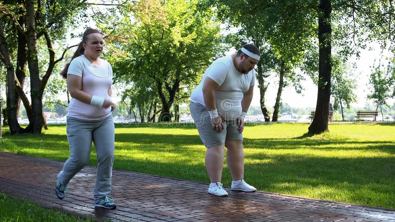 逃脱肥胖人的快乐的胖的女孩在跑步疲倦了,用尽以后锻炼 库存图片
