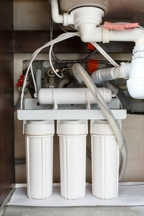 逆渗透作用水净化系统在家 在厨房水槽下的水净化过滤器的设施在碗柜 图库摄影