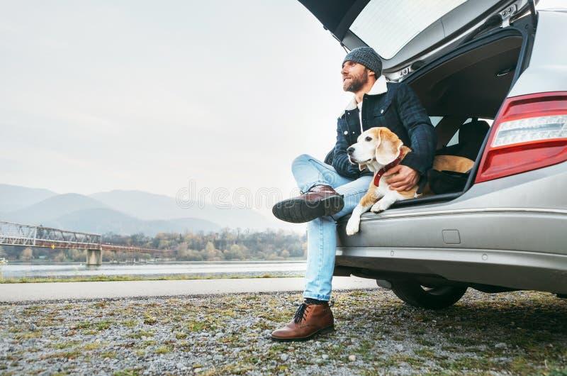 选址与在车厢的小猎犬的衣服暖和的面包人 旅行与宠物概念图象 免版税库存图片