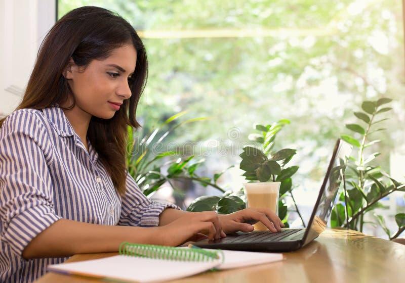 选址在咖啡馆饮用的咖啡和研究膝上型计算机的年轻女人 免版税库存照片