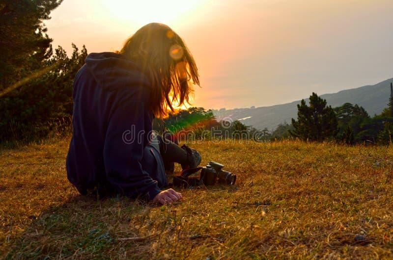 选址在山的草的女孩在她的头发的太阳 免版税库存照片