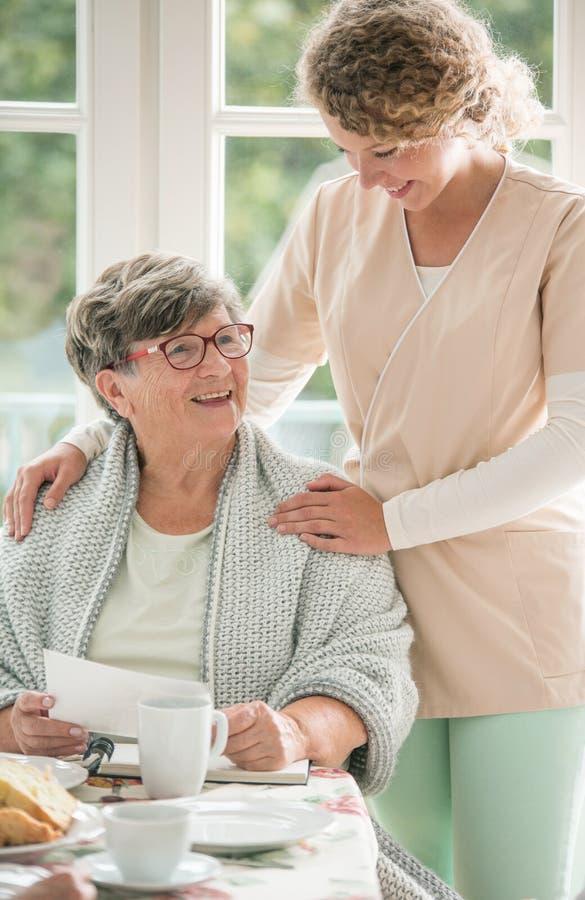 选址在桌上和微笑对她的年轻护士的正面资深夫人 库存照片