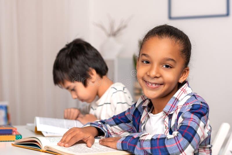 选址在桌上户内和做他们的家庭作业的女小学生和男小学生 免版税库存照片