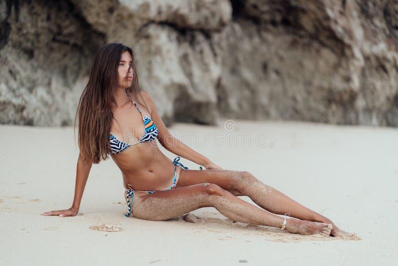 选址在白色沙滩的色的游泳衣的年轻性感的运动的女孩 免版税图库摄影