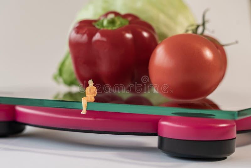 选址微型妇女的形象在重量的数字电子体重计人体 在浅深度的新鲜蔬菜 免版税图库摄影