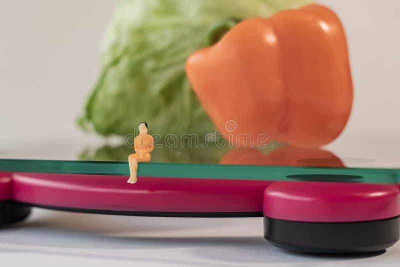 选址微型妇女的形象在重量的数字电子体重计人体 在浅深度的新鲜蔬菜 免版税库存照片