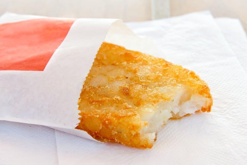 选拔在纸袋的部分地被吃的马铃薯煎饼 免版税库存照片