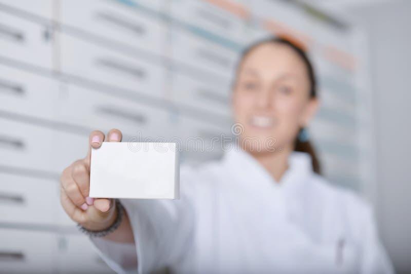 选拔有白色实验室外套的咧嘴笑的药剂师阻止箱子的 库存照片