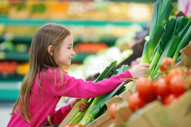 选择一个韭葱的小女孩在食品店或超级市场 免版税库存照片