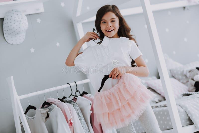 选择一件礼服的小逗人喜爱的女孩在卧室 免版税图库摄影